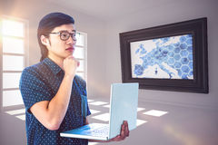 Composite image of thoughtful hipster using his laptop Stock Image