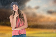 Composite image of thoughtful woman wearing hat with finger on chin Royalty Free Stock Photo