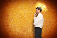 Composite image of thoughtful young businessman looking away Stock Image