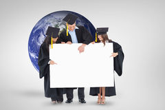 Composite image of three graduates pointing to the blank sign Royalty Free Stock Image
