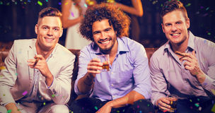 Composite image of three happy friends having cigar and whisky in bar. Three happy friends having cigar and whisky in bar against flying colours Royalty Free Stock Image