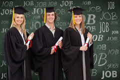 Composite image of three smiling students in graduate robe holding a diploma Stock Photo