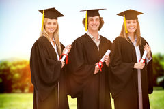 Composite image of three smiling students in graduate robe holding a diploma Royalty Free Stock Photos