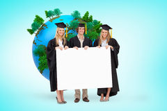 Composite image of three students in graduate robe holding a blank sign Stock Photos