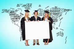 Composite image of three students in graduate robe holding a blank sign Royalty Free Stock Photography