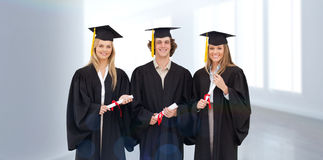 Composite image of three students in graduate robe holding a diploma Royalty Free Stock Photos