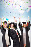 Composite image of three students in graduate robe raising their arms Royalty Free Stock Photos