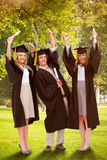 Composite image of three students in graduate robe raising their arms Royalty Free Stock Photo