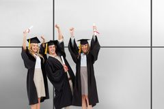 Composite image of three students in graduate robe raising their arms royalty free stock images