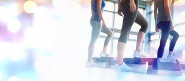 Composite image of three women in aerobics class. Three women in aerobics class against glowing background Stock Photo