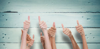 Composite image of thumbs raised and hands up. Thumbs raised and hands up  against painted blue wooden planks Stock Photos