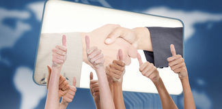 Composite image of thumbs raised and hands up. Thumbs raised and hands up against screen with image of handshake in blue interface royalty free stock photos