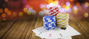 Composite image of tilt image of casino tokens with playing cards. Tilt image of casino tokens with playing cards against wooden table Royalty Free Stock Photography