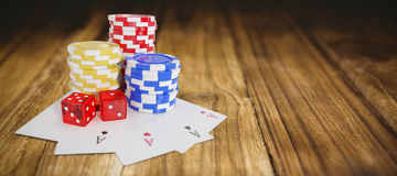 Composite image of tilt image of casino tokens with playing cards and dice. Tilt image of casino tokens with playing cards and dice against wooden table Royalty Free Stock Photos