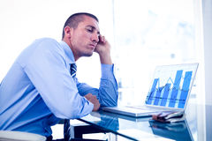 Composite image of tired businessman looking at his laptop Stock Photo