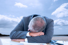 Composite image of tired businessman resting on desk Royalty Free Stock Photos