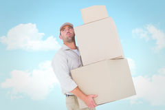 Composite image of tired delivery man carrying stack boxes Royalty Free Stock Images