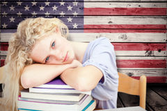 Composite image of tired teeenager sleeping in a library Royalty Free Stock Images