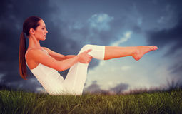 Composite image of toned woman doing the boat pose in fitness studio. Toned woman doing the boat pose in fitness studio against blue sky over grass Stock Photography