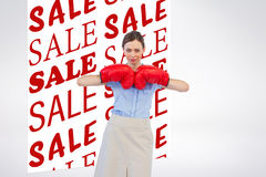 Composite image of tough businesswoman posing with red boxing gloves Royalty Free Stock Photo