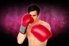 Composite image of tough man wearing red boxing gloves punching to camera Stock Photos
