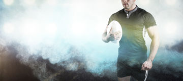 Composite image of tough rugby player holding ball. 3D Tough rugby player holding ball against digitally generated image of color powder royalty free stock photos