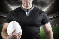 Composite image of tough rugby player holding ball Stock Photos