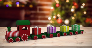 Composite image of train model carrying gift boxes Stock Photo