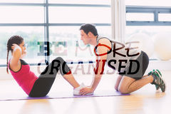 A Composite image of trainer helping woman do abdominal crunches in gym. Trainer helping women do abdominal crunches in gym against be more organised Stock Photo