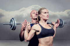 Composite image of trainer helping woman for lifting crossfit. Trainer helping women for lifting crossfit against clouds in a room Royalty Free Stock Photo