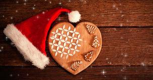Composite image of twinkling stars. Twinkling stars against ginger bread on wooden board by santa hat Stock Photos