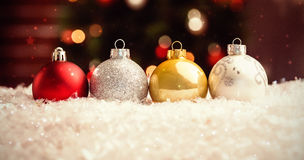 Composite image of twinkling stars. Twinkling stars against multi colored christmas baubles lined up Stock Photos