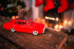 Composite image of twinkling stars. Twinkling stars against red toy car with pine cone on wooden table Stock Image