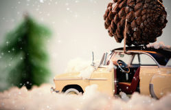 Composite image of twinkling stars. Twinkling stars against toy car carrying pine cone on fake snow Royalty Free Stock Photo