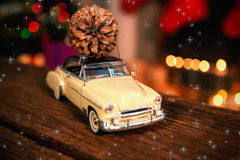 Composite image of twinkling stars. Twinkling stars against toy car with pine cone on wooden table Stock Images