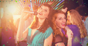 Composite image of two beautiful women singing song together Stock Photo