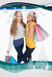 Composite image of two beautiful young women holding shopping bags Royalty Free Stock Photos