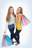 Composite image of two beautiful young women holding shopping bags Stock Images