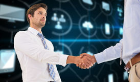 Composite image of two businessmen shaking hands in office. Two businessmen shaking hands in office against apps interface Stock Images