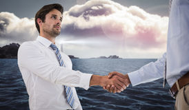 Composite image of two businessmen shaking hands in office. Two businessmen shaking hands in office against calm sea with lighthouse Royalty Free Stock Photos