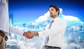Composite image of two businessmen shaking hands in office. Two businessmen shaking hands in office against city skyline Royalty Free Stock Image