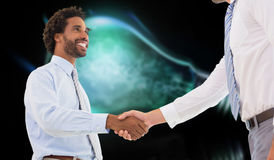 Composite image of two businessmen shaking hands in office. Two businessmen shaking hands in office against glowing light bulb Stock Images