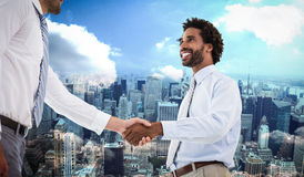 Composite image of two businessmen shaking hands in office. Two businessmen shaking hands in office against new york Stock Photos