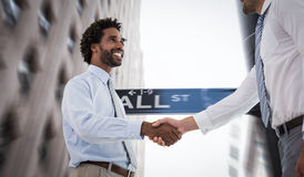 Composite image of two businessmen shaking hands in office Royalty Free Stock Photo