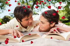 Composite image of two friends looking at each other while reading books on a blanket Stock Photo