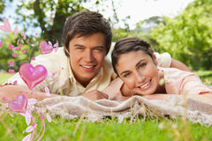 Composite image of two friends lying together on a blanket while smiling Stock Image