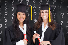 Composite image of two friends stand together after graduating Royalty Free Stock Photography