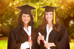 Composite image of two friends stand together after graduating Royalty Free Stock Photo