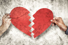 Composite image of two hands holding broken heart Stock Photo