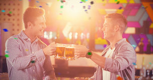 Composite image of two male friends toasting beer mugs at bar counter Royalty Free Stock Photos